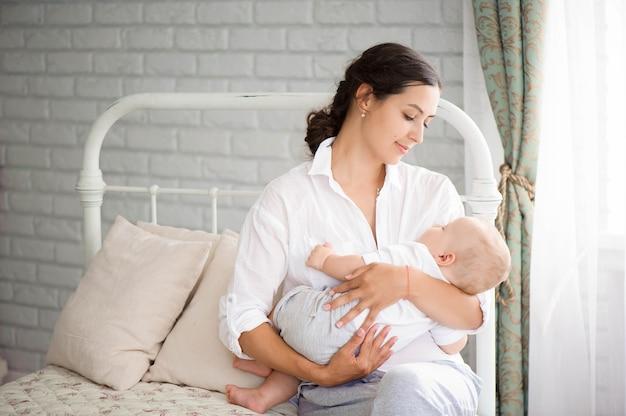 Bebê dormindo no peito da mãe. linda jovem mãe se recuperando após o parto. jovem mãe acariciando o bebê com ternura.