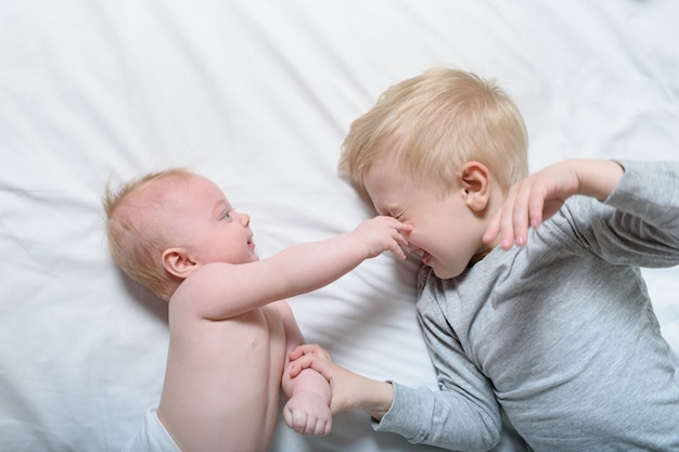 Bebê e irmão mais velho a sorrir estão deitados na cama. eles brincam, divertem e interagem. vista do topo