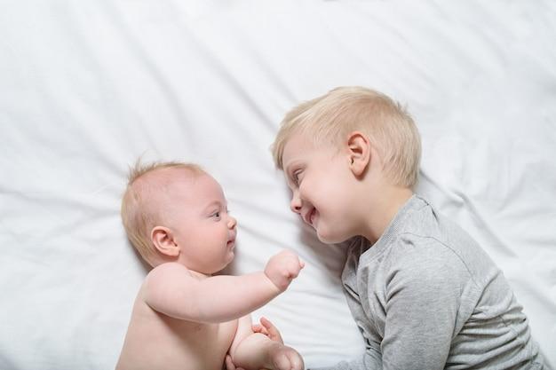 Bebê e irmão mais velho a sorrir estão deitados na cama. eles brincam, se comunicam e interagem. vista do topo