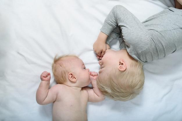 Bebê e irmão mais velho a sorrir estão deitados na cama. engraçado e interagir. vista do topo