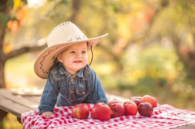 Bebê e maçãs na natureza. pequeno agricultor engraçado e colheita de maçãs