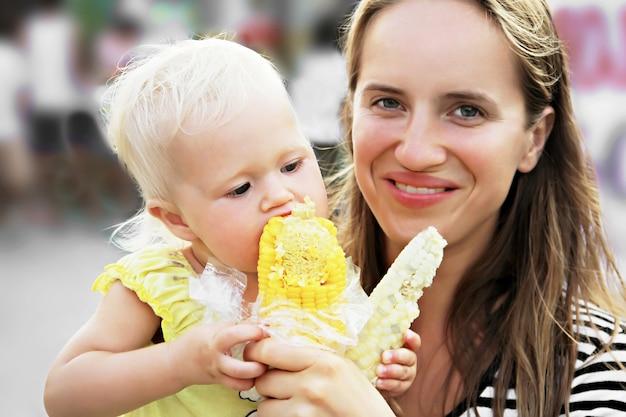 Bebê e mãe comendo milho
