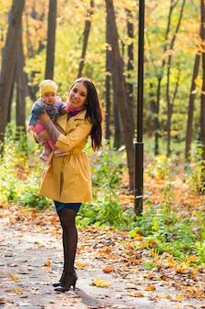 Bebê e mãe de família feliz riem com folhas no outono de natureza.