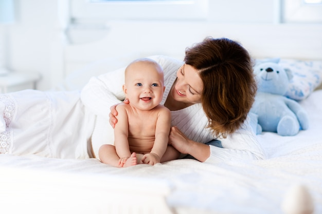 Bebê e mãe em casa na cama. mãe e filho