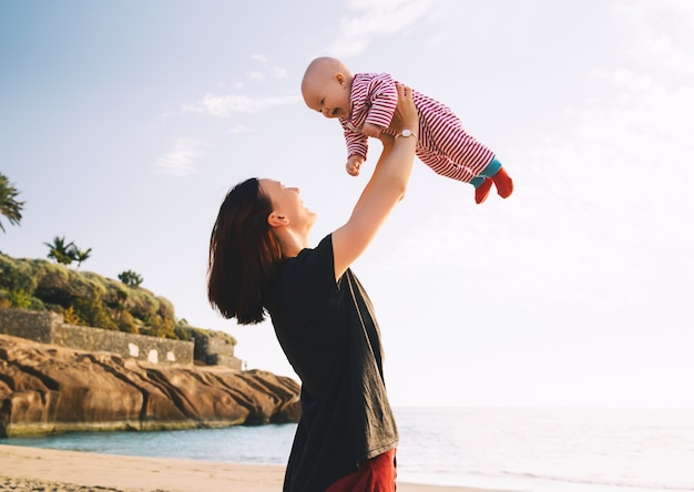 Bebê e mãe no mar em dia de verão família feliz caminhando ao ar livre na natureza