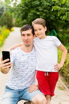 Bebê e pai feliz tiram selfies.