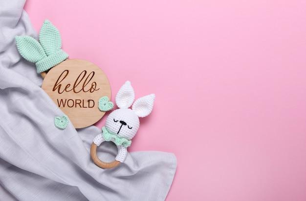 Bebê eco brinquedos de madeira tablet de madeira olá mundo, fralda cinza bebê de musselina em fundo rosa