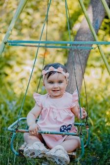 Bebê elegante com vestido roxo sentado em uma cadeira de balanço no parque