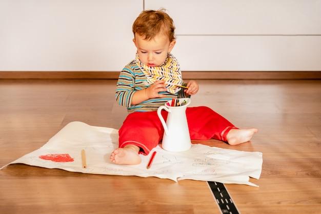 Bebê em casa usando lápis de cor para pintar em papel
