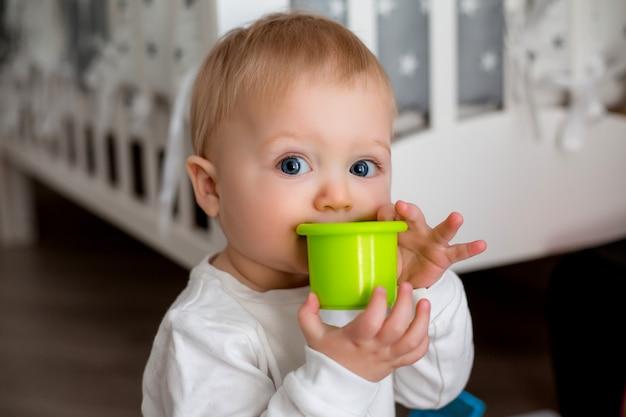 Bebê em roupas brancas está sentado no chão no quarto das crianças e brincando com brinquedos