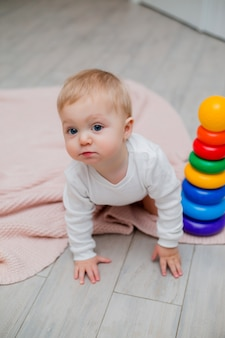 Bebê em roupas brancas, sentada no chão em um cobertor de malha e brincando com brinquedos educativos, espaço para texto