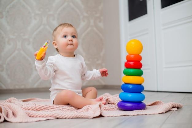 Bebê em roupas brancas, sentada no chão em um cobertor de malha e brincando com brinquedos educativos