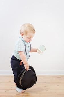 Bebê em shorts de chapéu preto, camisa e suspensórios em casa