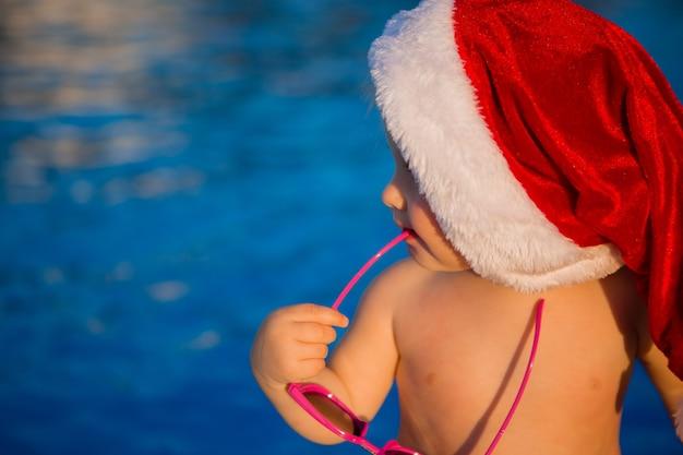 Bebê em um chapéu de papai noel e óculos de sol na piscina