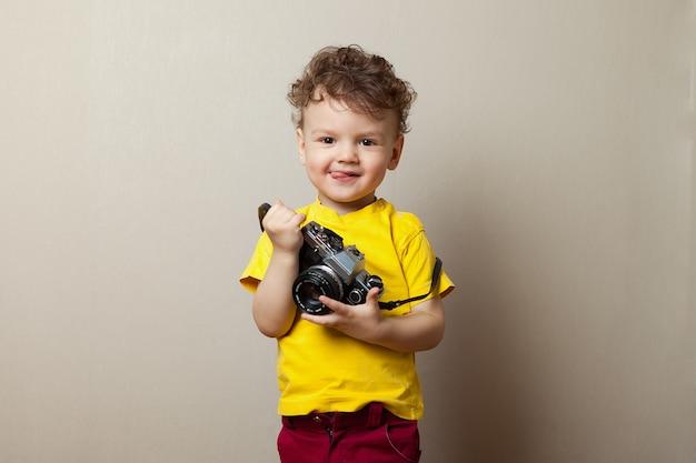 Bebé em um t-shirt amarelo com uma câmera em suas mãos.