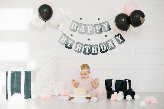 Bebê em um vestido rosa tenta o bolo
