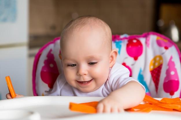 Bebê em uma cadeira de criança, comer legumes