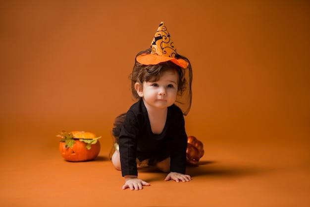 Bebê em uma fantasia de bruxa para o halloween