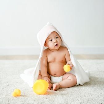 Bebê em uma toalha de banho com patos de borracha