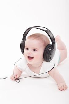 Bebê encantador em um fundo branco com fones de ouvido, ouvindo