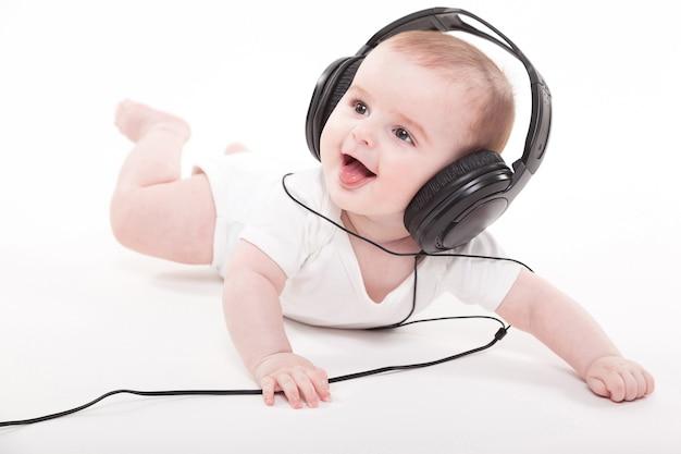 Bebê encantador em um fundo branco com fones de ouvido