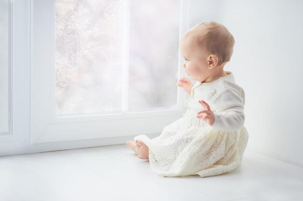 Bebé encaracolado louro da criança que olha através de uma janela.