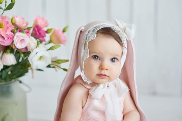 Bebê engraçado bonito com orelha de coelho. coelho da páscoa. menina bonito 6 meses na cama