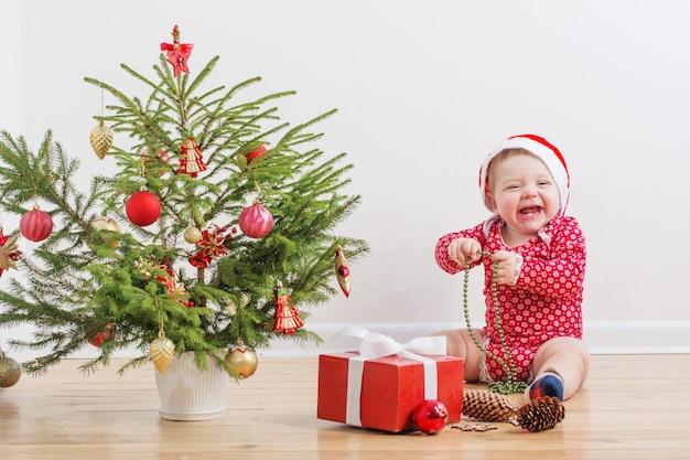 Bebê engraçado com pouco de abeto de natal em casa