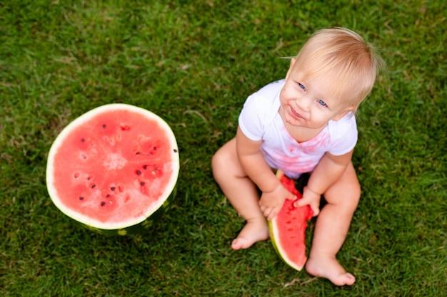 Bebê engraçado comer melancia ao ar livre no parque. bebê, bebê, comida saudável