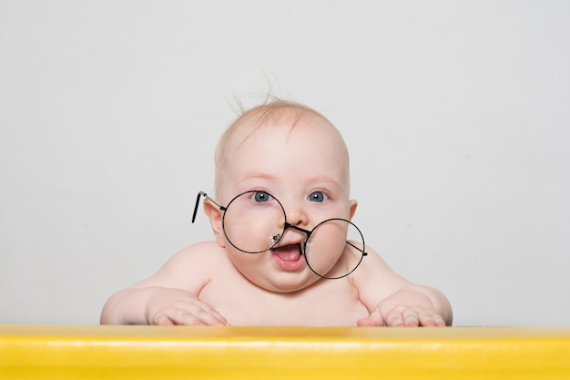 Bebê engraçado em grandes copos redondos na mesa