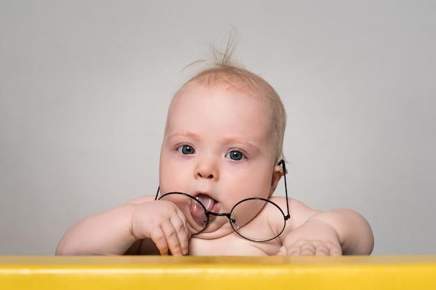 Bebê engraçado em grandes copos redondos na mesa.