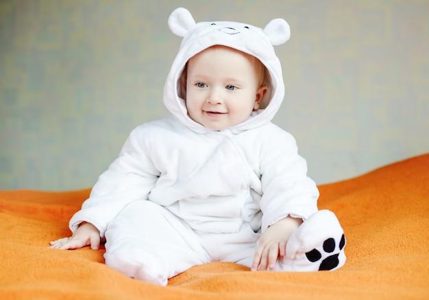 Bebê engraçado fantasiado de urso no sofá