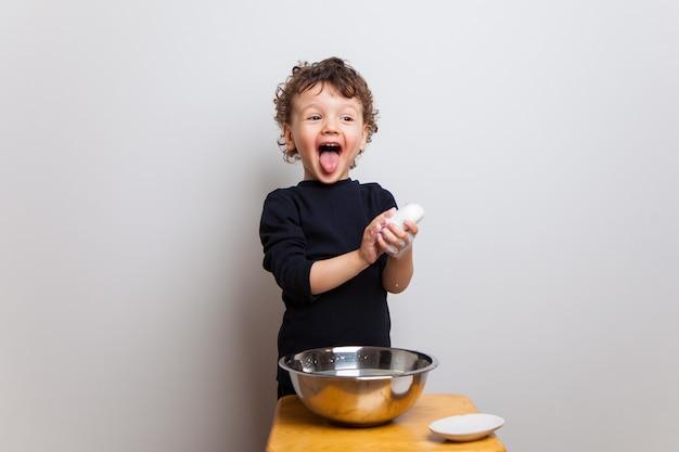 Bebê engraçado lava as mãos com sabão em uma tigela de água. mãos protegem.