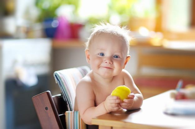 Bebé engraçado que come a comida saudável (a maçã)