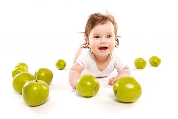 Bebê engraçado rodeado por maçãs verdes