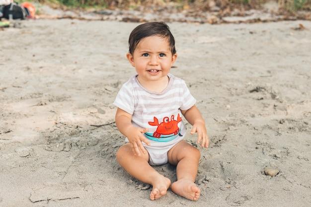 Bebê engraçado sentado na areia da praia