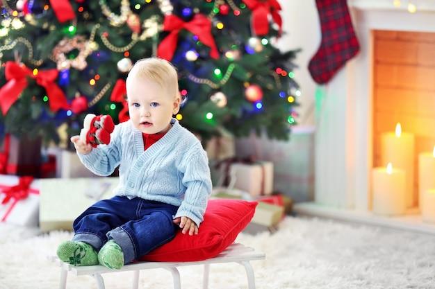 Bebê engraçado sentado no trenó, árvore de natal e lareira na