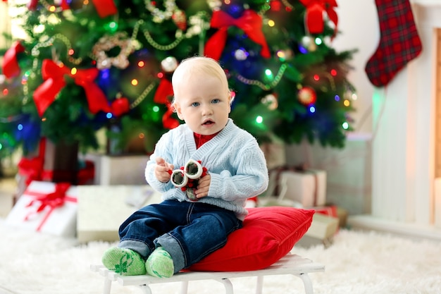 Bebê engraçado sentado no trenó e árvore de natal e lareira na superfície