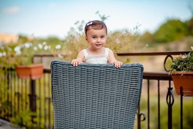 Bebé espantado com adoráveis olhos azuis numa cadeira de palha a sorrir