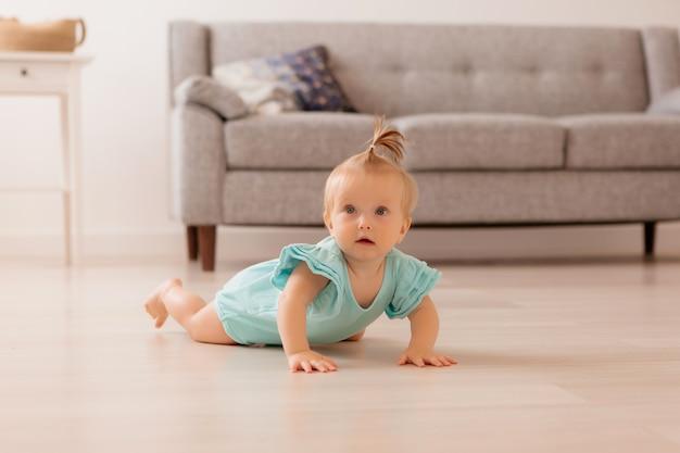Bebê está deitado no chão da sala