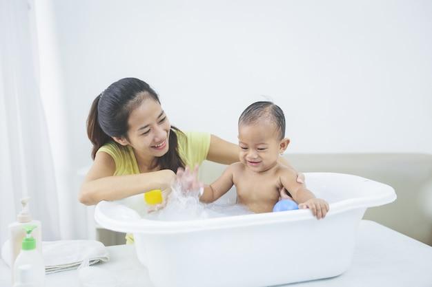 Bebê está sendo banhado por sua mãe