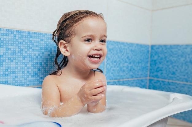 Bebê feliz alegre da criança do divertimento que toma um banho que joga com bolhas da espuma.