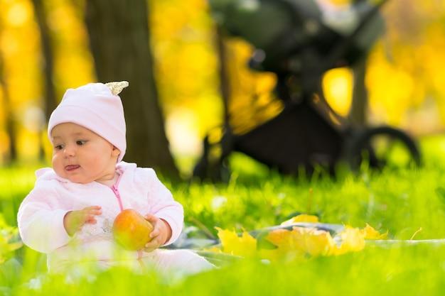 Bebê feliz ao ar livre em um parque no outono, sentado em um tapete na grama verde fresca, segurando uma maçã em uma visão de baixo ângulo, mostrando as coloridas árvores amarelas atrás