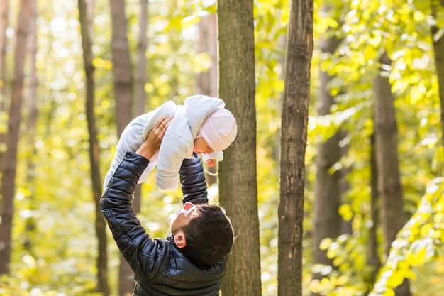 Bebê feliz com o pai ao ar livre na primavera