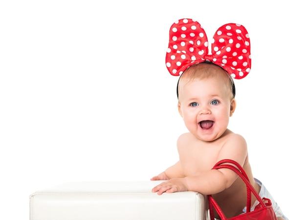 Bebê feliz com um laço de bolinhas na cabeça