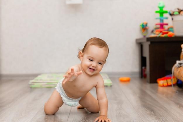 Bebê feliz de 11 meses rasteja no chão e ri. a criança está sentada no chão.