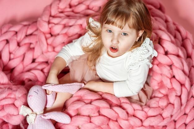 Bebê feliz em fundo rosa coral olha surpreso. com espaço de texto livre.