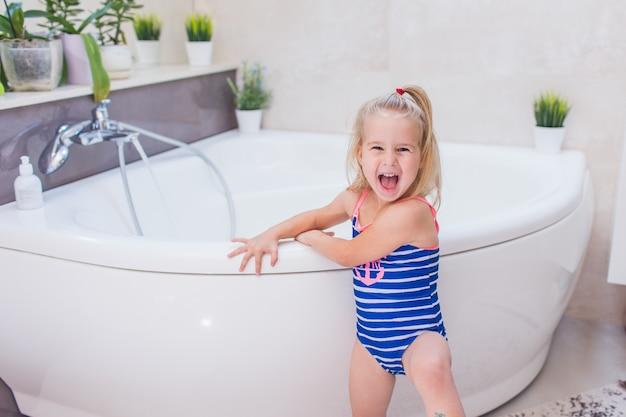 Bebê feliz em um maiô azul whetu ficar perto da banheira no banheiro e gritando com um sorriso.