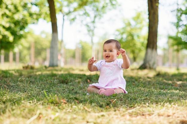 Bebê feliz em um vestido rosa senta-se na grama do parque. bebé pequeno que plaing na grama verde.