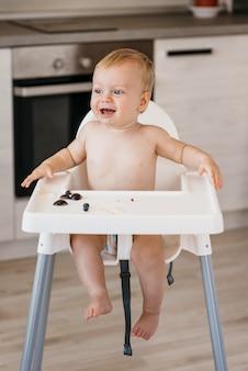 Bebé feliz na cadeira alta a escolher que fruta comer